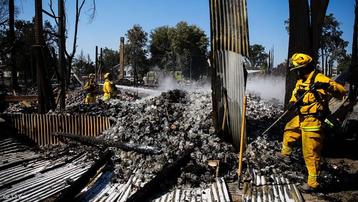 Firefighters work to contain embers at a candle factory destroyed in the Clayton Fire in Lower Lake, California, August 15th, 2016.  A northern California wildfire grew rapidly over the weekend, destroying homes and forcing 4,000 residents to flee, authorities said.  / AFP / GABRIELLE LURIE        (Photo credit should read GABRIELLE LURIE/AFP/Getty Images)