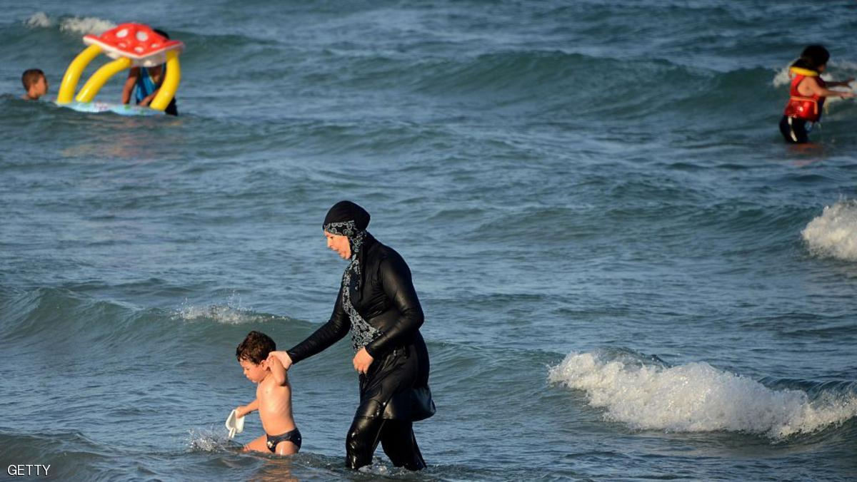 "A Tunisian woman wearing a ""burkini"", a full-body swimsuit designed for Muslim women, walks in the water with a child on August 16, 2016 at Ghar El Melh beach near Bizerte, north-east of the capital Tunis.  / AFP / FETHI BELAID        (Photo credit should read FETHI BELAID/AFP/Getty Images)"